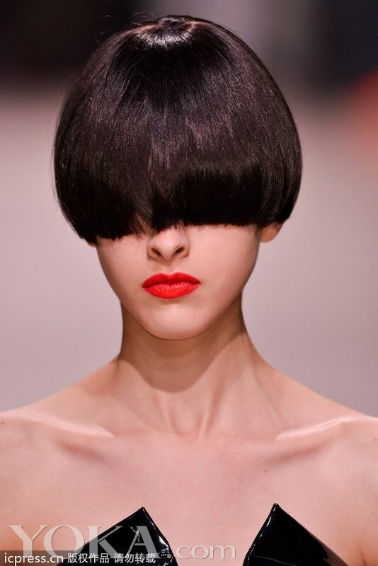 Undercover2014春夏巴黎时装周秀场绝对是创意爆棚。日本设计师高桥盾 (Jun Takahashi) 设计的服装一向以大胆叛逆著称,此次模特们的妆容发型更是不走寻常路线,中性、朋克、霸气、冷艳!我们见过顶着蘑菇头的模特走秀,可是你见过模特们顶着遮住眼睛的锅盖头发型走秀吗?这完全是在考验模特们的T台经验啊。模特们清一色的锅盖头短发,齐刘海统一达到鼻尖,盖住耳朵,露出一半的鼻子,眼睛和半张脸都被遮得严严实实。再化上浓烈的红唇,与黑亮的短发形成鲜明的对比,没有其它花哨的元素,却十分震撼!